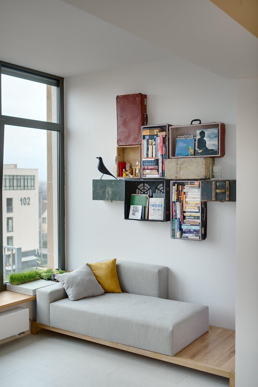 Hình ảnh góc đọc sách ngập tràn ánh sáng với sofa văng mà xám, giá kệ gắn tường