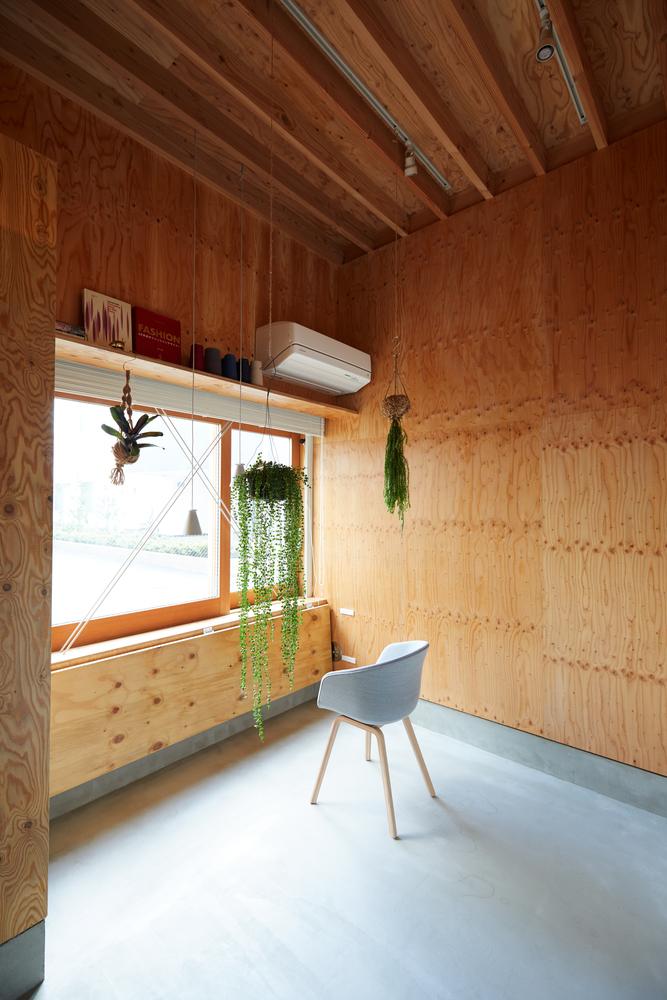 Hình ảnh phòng làm việc thoáng sáng trong ngôi nhà 43m2 với ghế tựa, bàn gỗ dài gập gọn vào cửa sổ kính, chậu cây treo trang trí