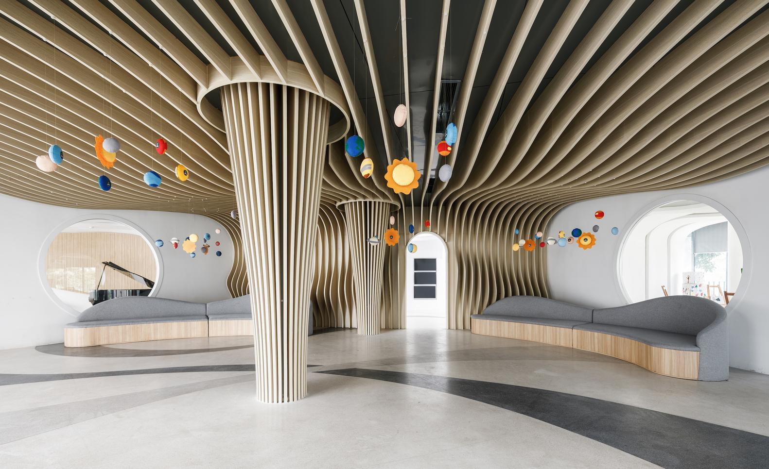 Hình ảnh bên trong trường mẫu giáo với hệ trần, cột bằng gỗ màu sáng, trang trí màu sắc bắt mắt