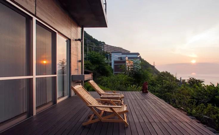 Hình ảnh hiên nhà được bài trí đơn giản với ghế tựa thư giãn và bàn trà gỗ, phía trước là cảnh quan thiên nhiên tươi đẹp