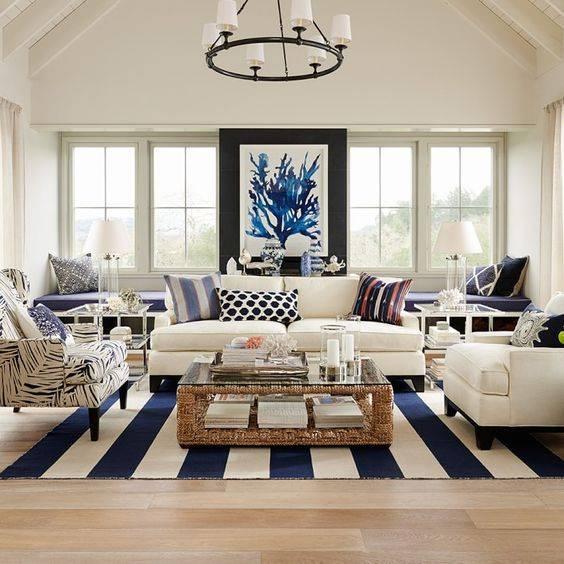 Hình ảnh phòng khách ấn tượng với tranh nghệ thuật trừu tượng cỡ lớn, ghế ngồi bọc vải họa tiết, thảm trải kẻ sọc, cửa kính lớn
