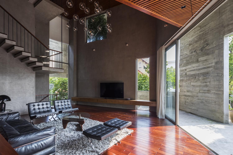 Hình ảnh phòng khách biệt thự ở Hạ Long với sofa đen, bàn trà kính nhỏ đặt trên thảm trải lông, đèn trang trí thủy tinh trong suốt