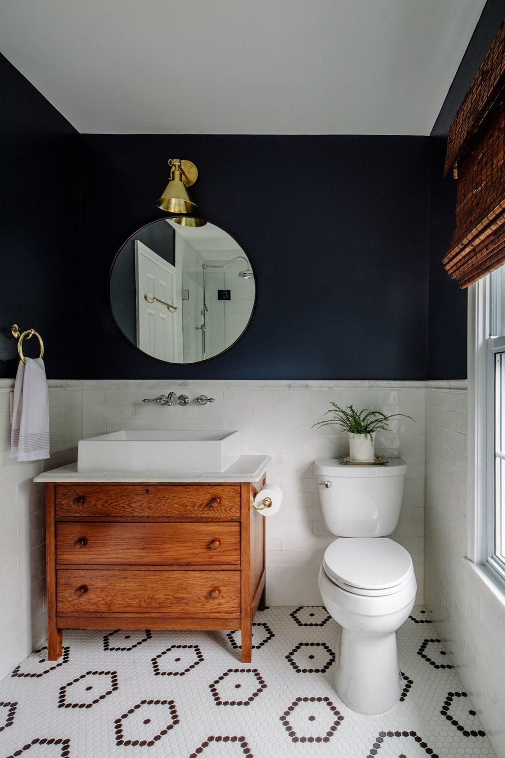 Hình ảnh phòng tắm nhỏ với mảng tường màu xanh navy ấn tượng, gạch lát họa tiết đen trắng, gương tròn, tủ gỗ ngăn kéo