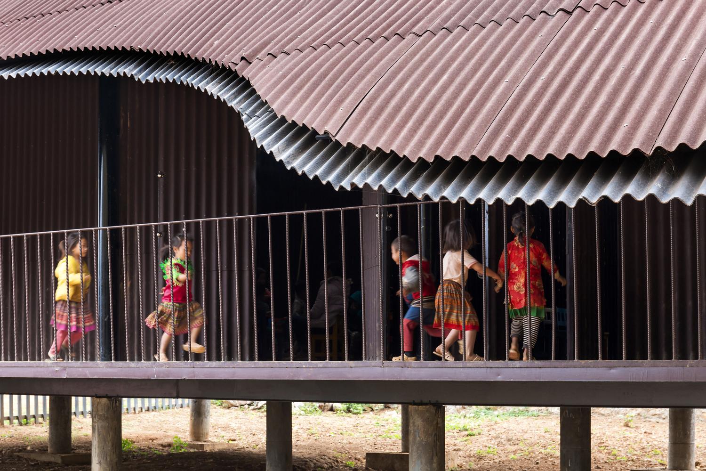 Hình ảnh cận cảnh mặt bên trường mầm non với mái tôn, trẻ nhỏ vui đùa ở hành lang