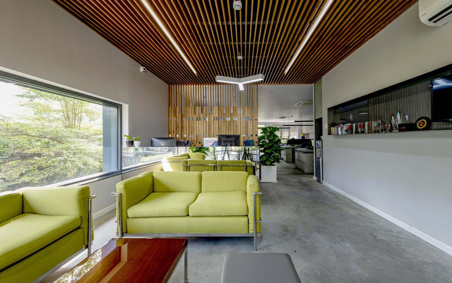 hình ảnh phòng tiếp khách trong tòa văn phòng với ghế sofa màu xanh lá cây