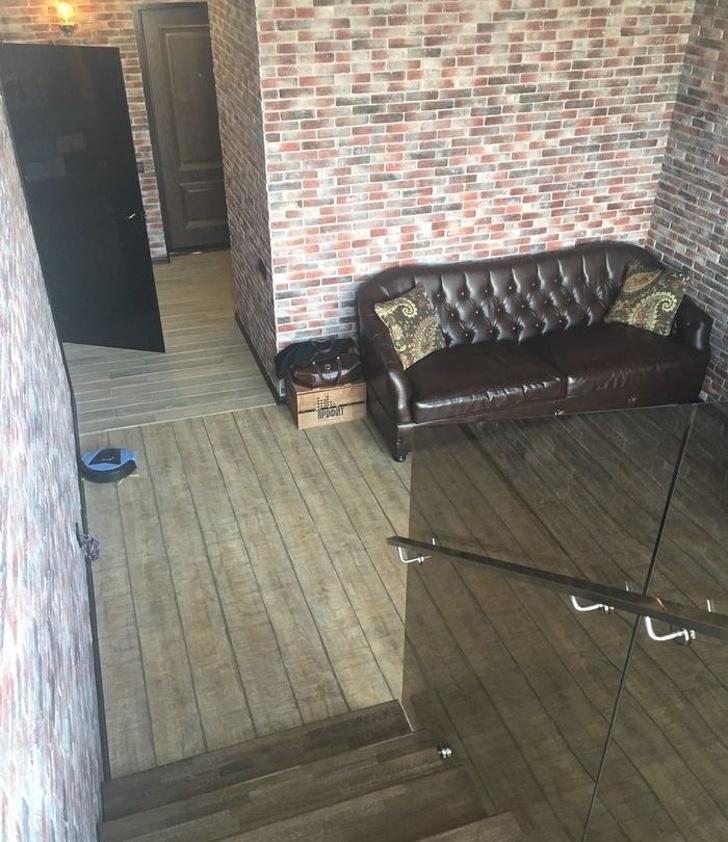 hình ảnh một căn phòng với sofa da đen cổ điển, tường gạch nung, bóng đèn sợi đốt