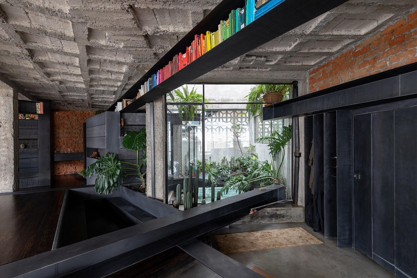 hình ảnh một góc phòng sinh hoạt chung trong căn hộ với kệ sách màu đen sát trần, cây xanh trang trí