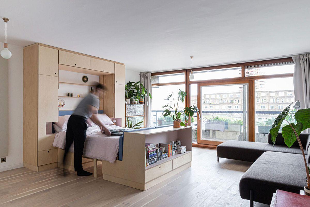 hình ảnh toàn cảnh không gian sinh hoạt trong căn hộ nhỏ ở London với ghế sofa màu ghi xám, giường gấp, cây xanh