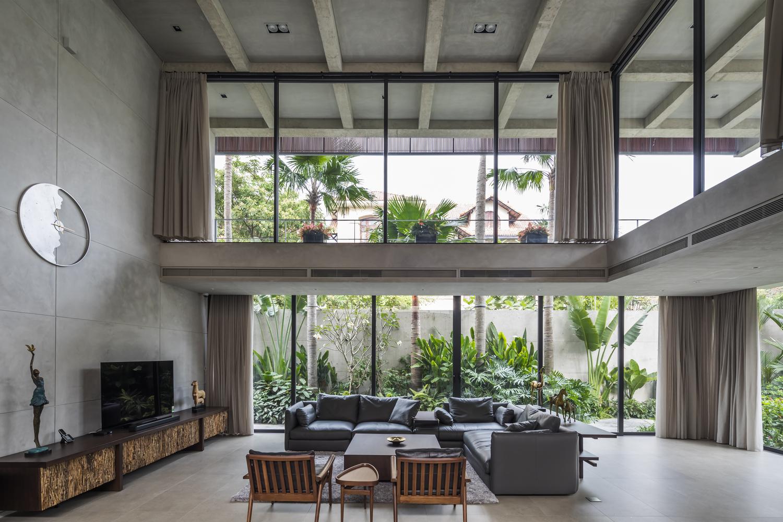 hình ảnh phòng khách rộng rãi, trần cao thoáng với bộ ghế sofa màu xám sang trọng, kệ tivi bằng gỗ, đồng hồ lớn treo tường