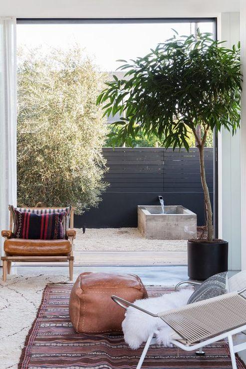 hình ảnh góc thư giãn ở sân sau nhà với ghế bành bọc da nâu, chăn lông trắng muốt, thảm trảm, cạnh đó là vòi nước chảy vào bể chứa bê tông nhỏ