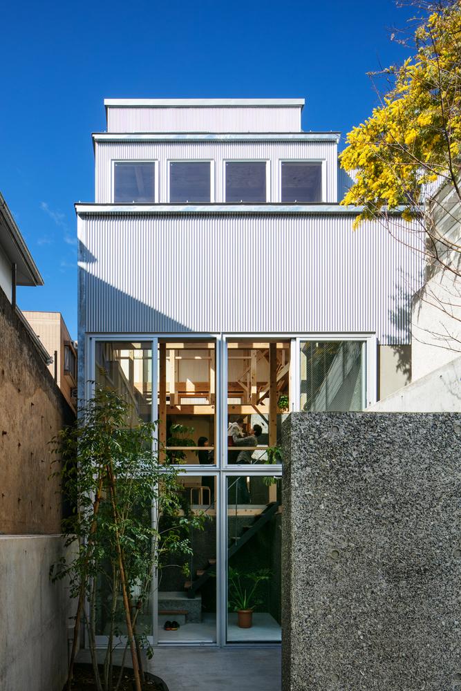 hình ảnh toàn cảnh mặt tiền ngôi nhà 69m2 ở Nhật Bản với tường bê tông lớn, cửa kính trong suốt, nội thất gỗ