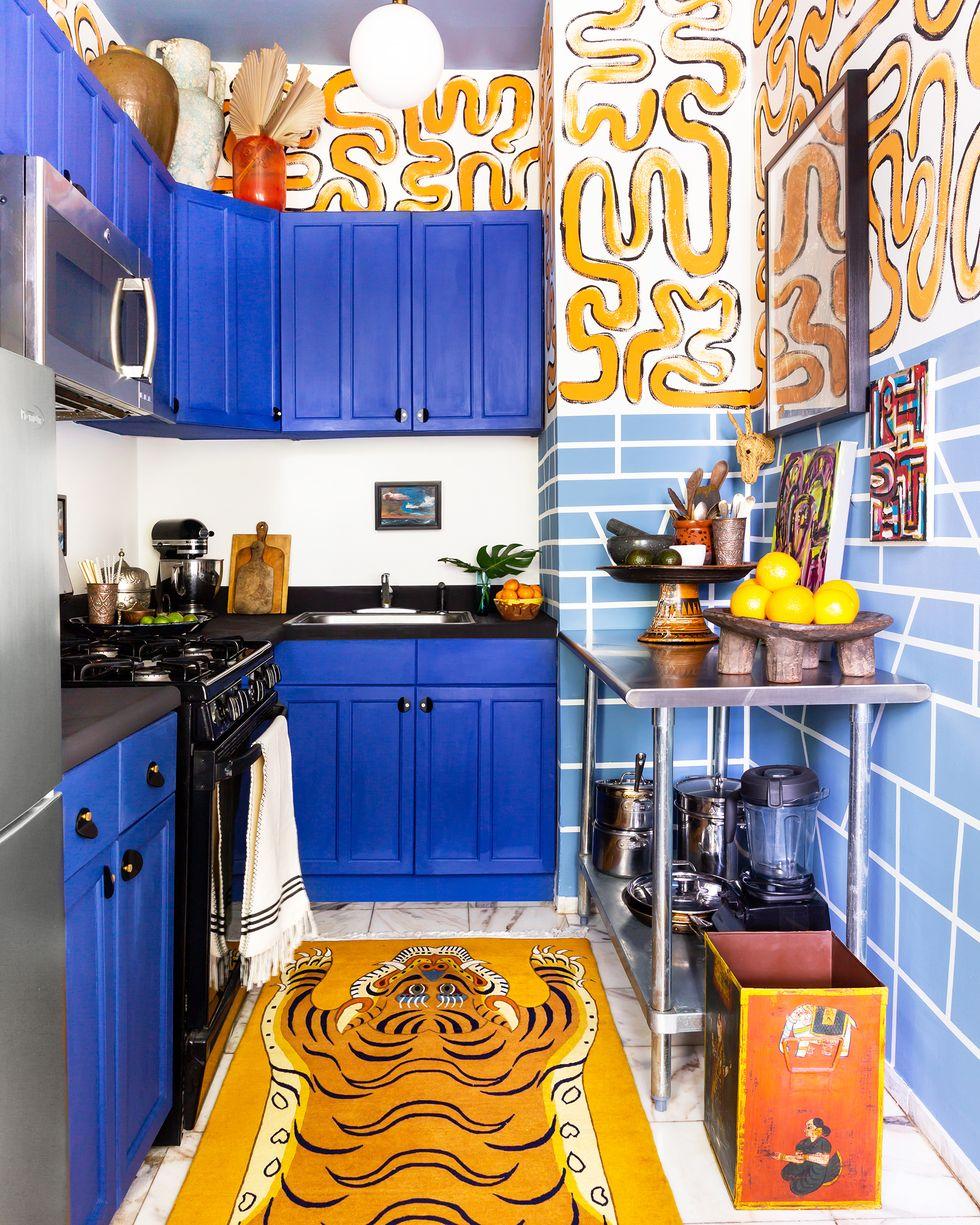 hình ảnh phòng bếp ấn tượng với hệ tủ màu xanh coban, thảm trải hình động vật, các chi tiết trang trí màu vàng trên tường nhà