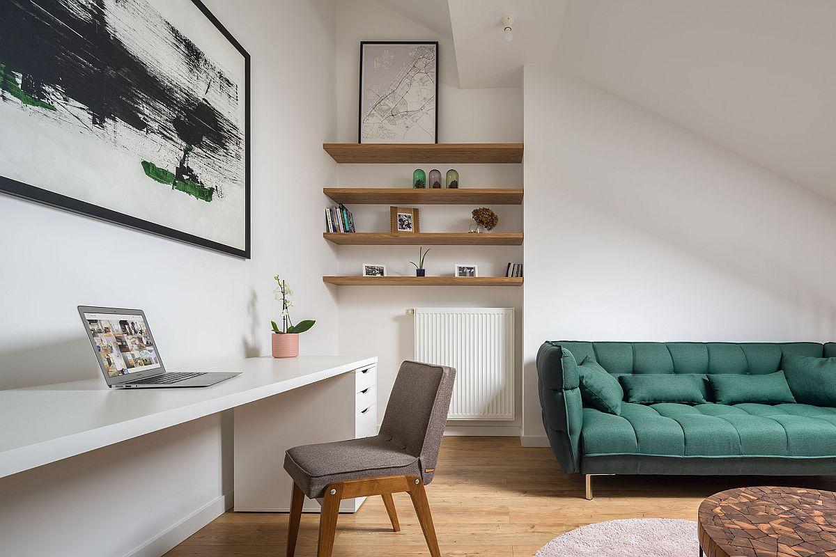 hình ảnh một góc phòng khách trên tầng lửng căn hộ nhỏ với sofa màu xanh lá, góc làm việc gọn gàng, tranh treo tường trừu tượng