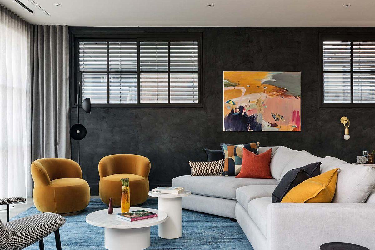 hình ảnh phòng khách với bức tường sơn đen, ghế sofa màu trắng, ghế bành và gối tựa màu vàng rực rỡ
