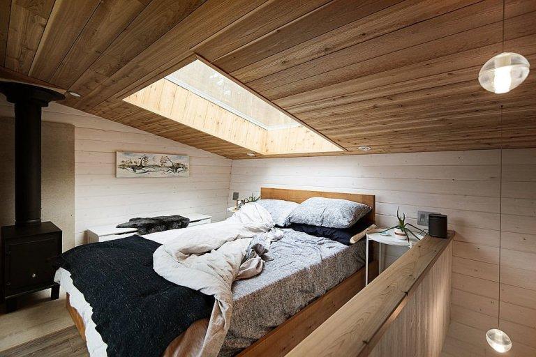 hình ảnh toàn cảnh phòng ngủ trên gác lửng nhà cabin gỗ ở Canada với cửa sổ kính trên mái, giường nệm êm ái, tranh treo tường, chậu cây đặt trên bàn nhỏ đầu giường