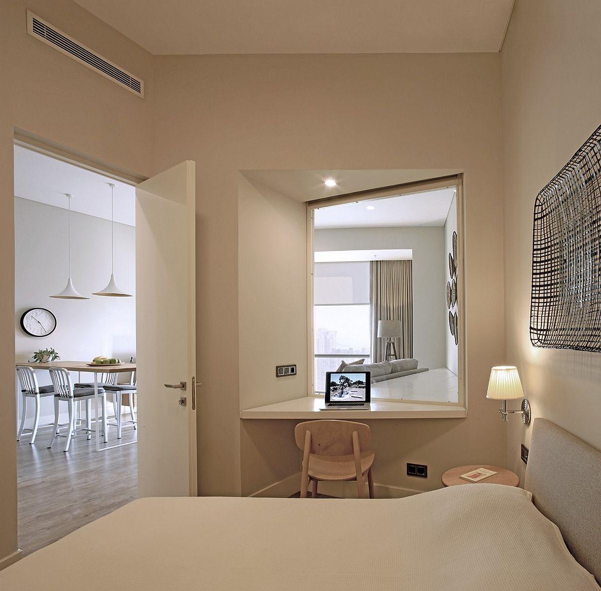 Hình ảnh một góc phòng ngủ màu trắng chủ đạo trong căn hộ nhỏ với bàn làm việc, trang điểm đặt ở góc phòng