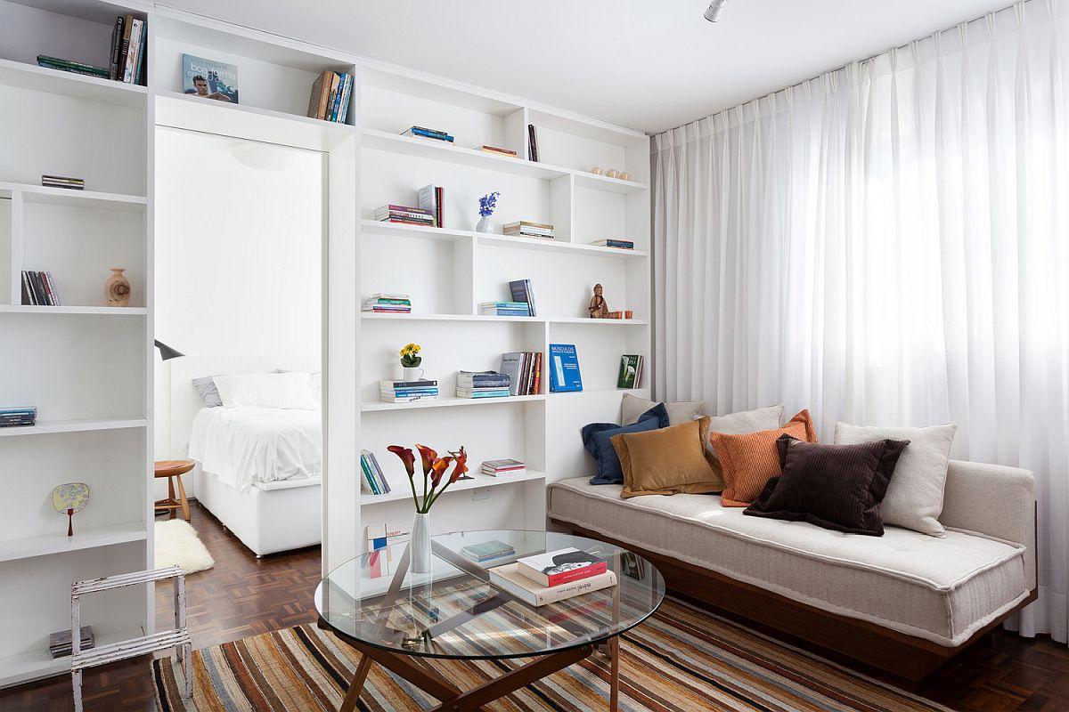 hình ảnh phòng khách căn hộ 30m2 với sofa mô-đun đặt cạnh cửa sổ kính lớn, giá sách màu trắng cao kịch trần, bàn trà kính, thảm trải kẻ sọc