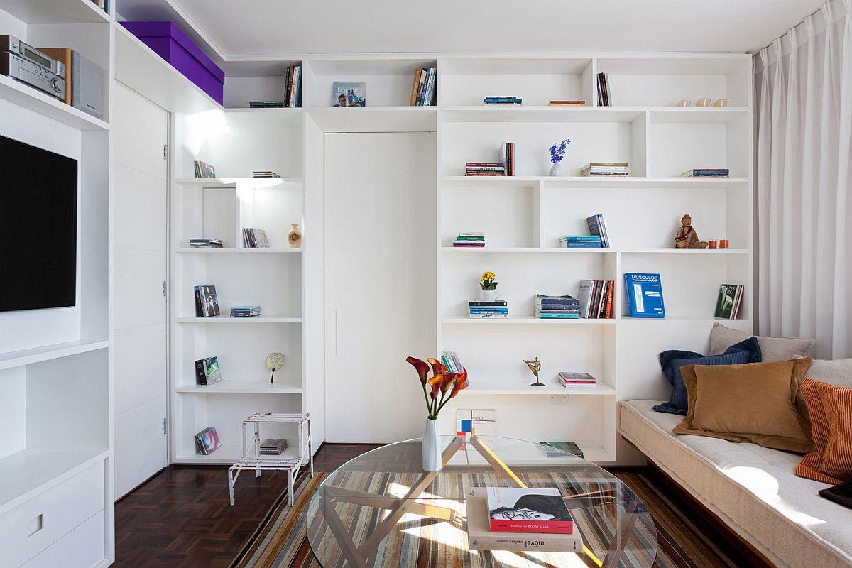 hình ảnh một góc phòng khách trong căn hộ nhỏ hẹp với kệ mở cao kịch trần, sofa mô đun, bàn trà kính tròn