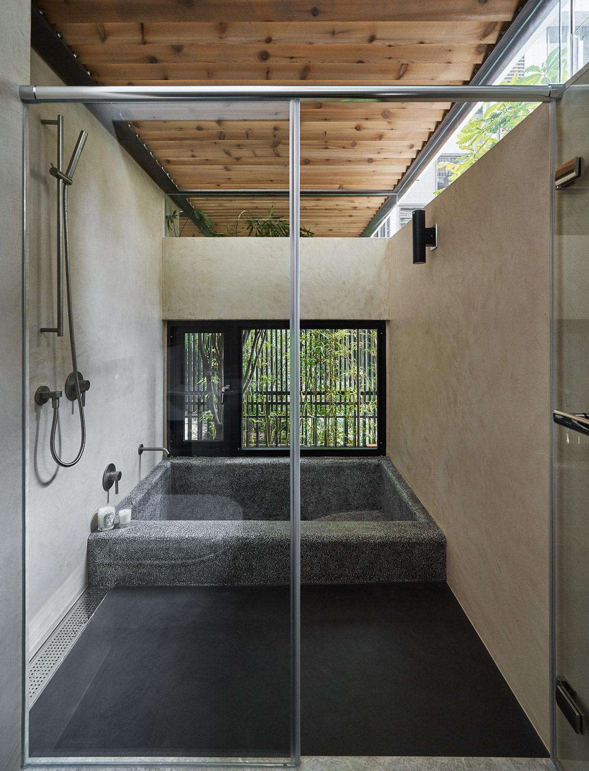 hình phòng tắm trong ngôi nhà Nhật với bồn tắm chìm, cửa kính trong suốt, dầm gỗ