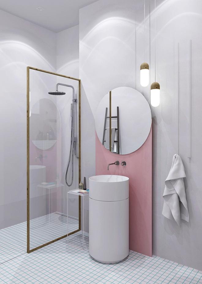 hình ảnh phòng tắm nhỏ hút mắt với mảng tường phía sau bồn rửa sơn màu hồng, gương tròn đơn giản, vách kính khung mạ vàng sáng bóng