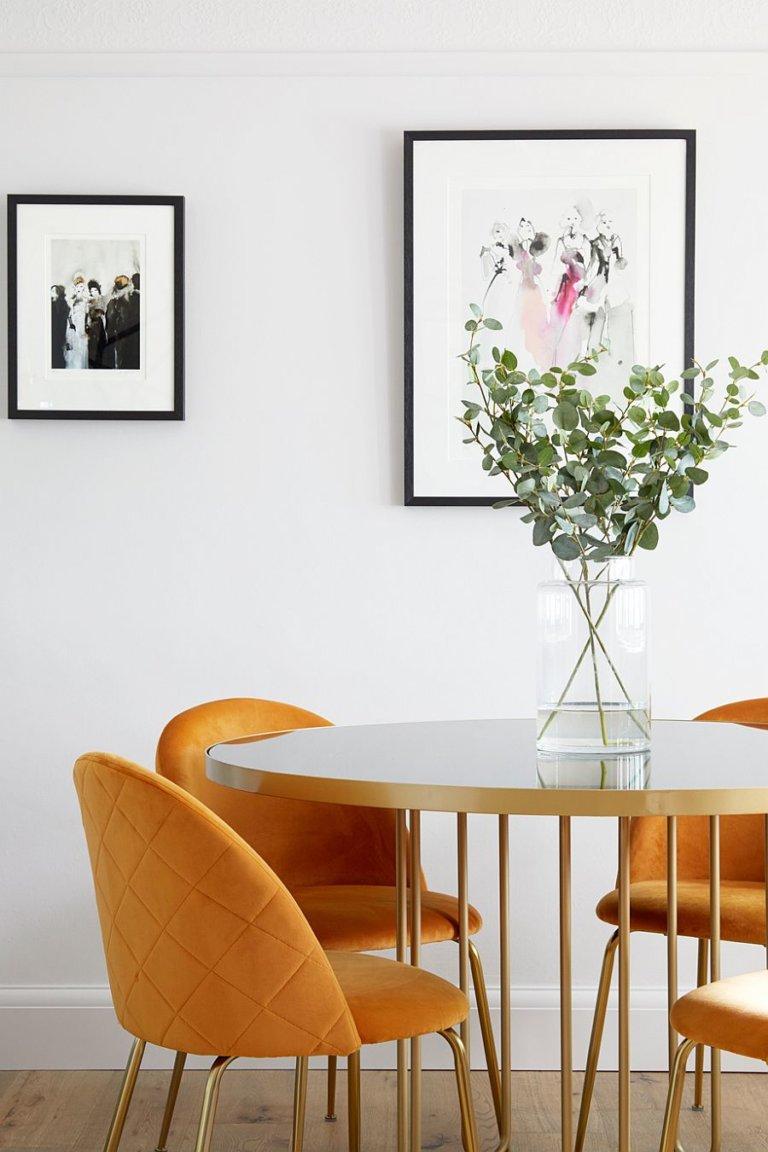 hình ảnh cận cảnh bàn ghế ăn với bàn tròn chân kim loại, ghế màu vàng, tranh khung đen treo tường