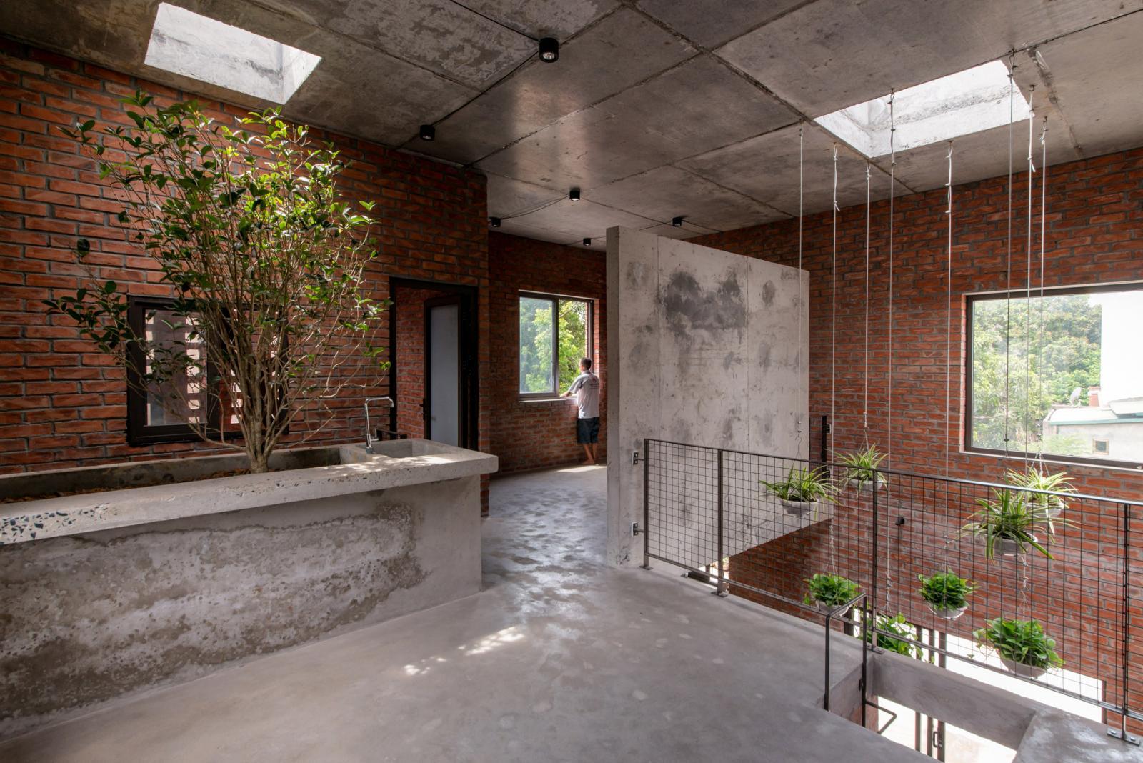 hình ảnh bên trong ngôi nhà gạch với tường gạch, bê tông thô xám, ô lấy sáng và thông gió, cây xanh tạo điểm nhấn