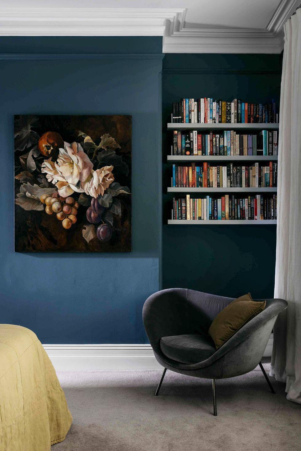 hình ảnh một góc phòng ngủ với kệ nổi trữ sách, ghế bành êm ái, ga trải giường màu vàng chanh nổi bật