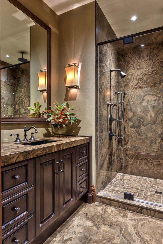 hình ảnh phòng tắm phong cách cổ điển với gạch ốp lát màu nâu, gương lớn gắn tường, đèn tường, chậu cây trang trí