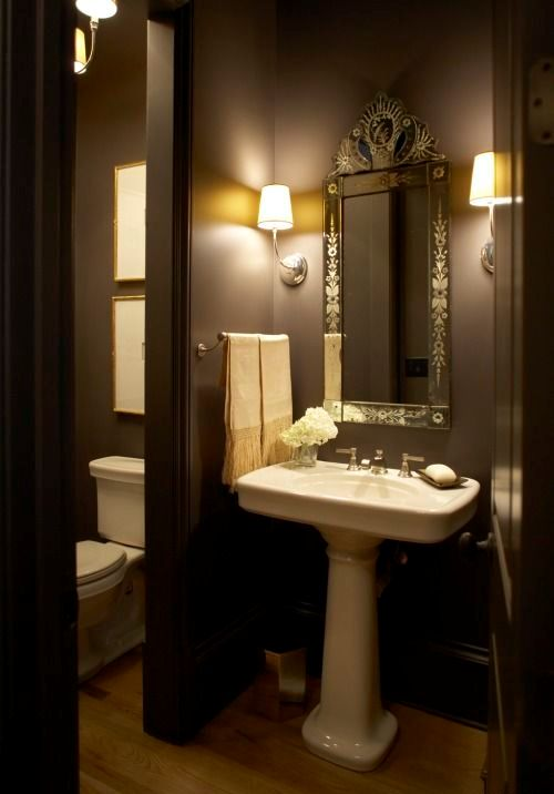 hình ảnh phòng tắm màu nâu sành điệu với gương soi kiểu dáng cổ điển, bồn rửa đứng và đèn tường ánh sáng vàng ấm áp.