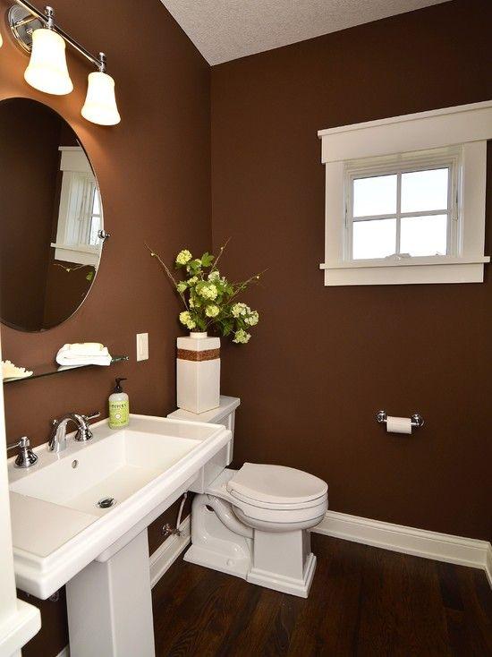 hình ảnh phòng tắm với tường sơn màu nâu sô cô la, sàn lát gỗ cùng tông màu, gương lớn gắn tường, đèn màu trắng