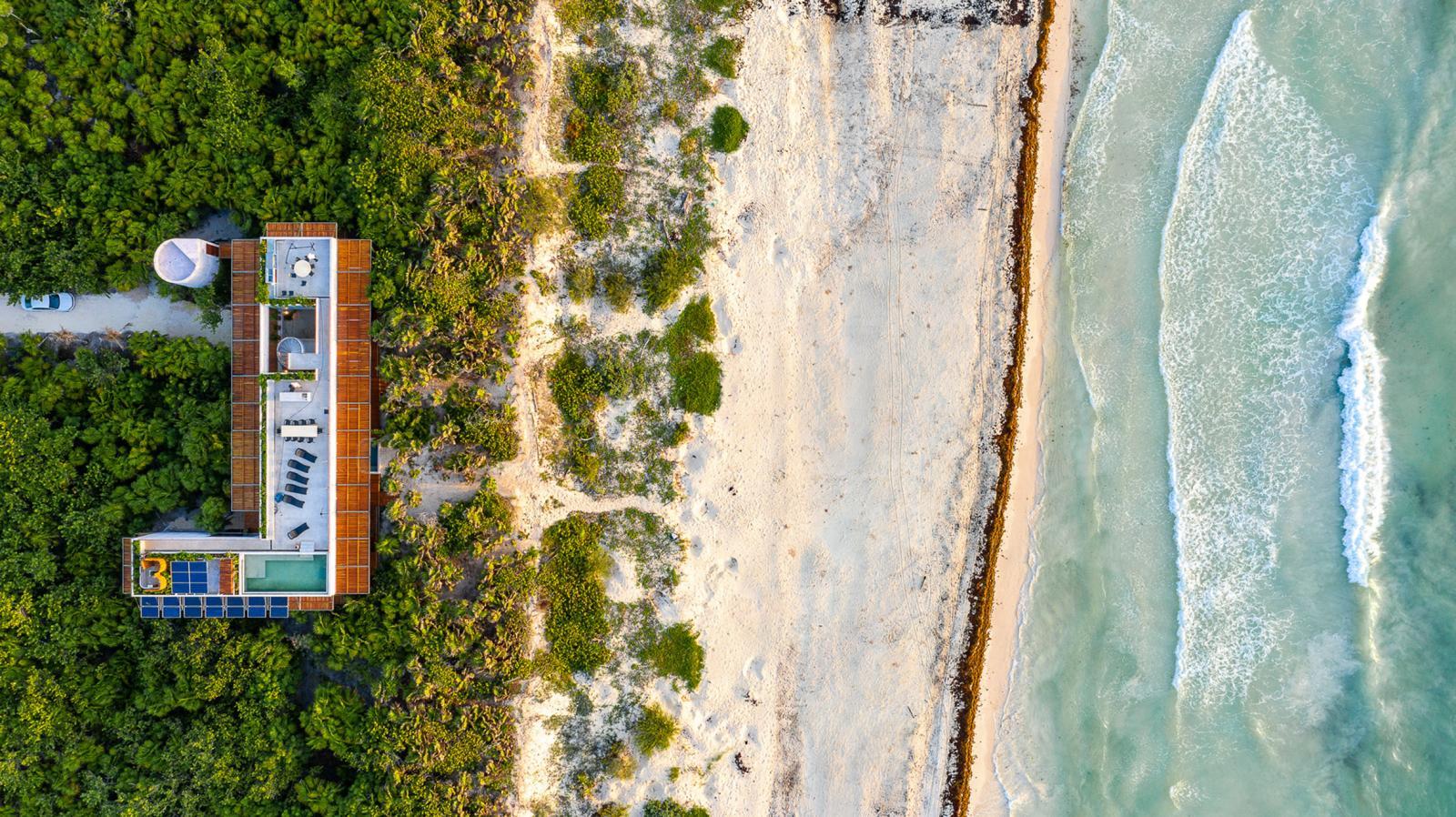 hình ảnh toàn cảnh ngôi nhà bê tông 2 tầng ở Mexico nhìn từ trên cao, xung quanh là rừng cây xanh tốt