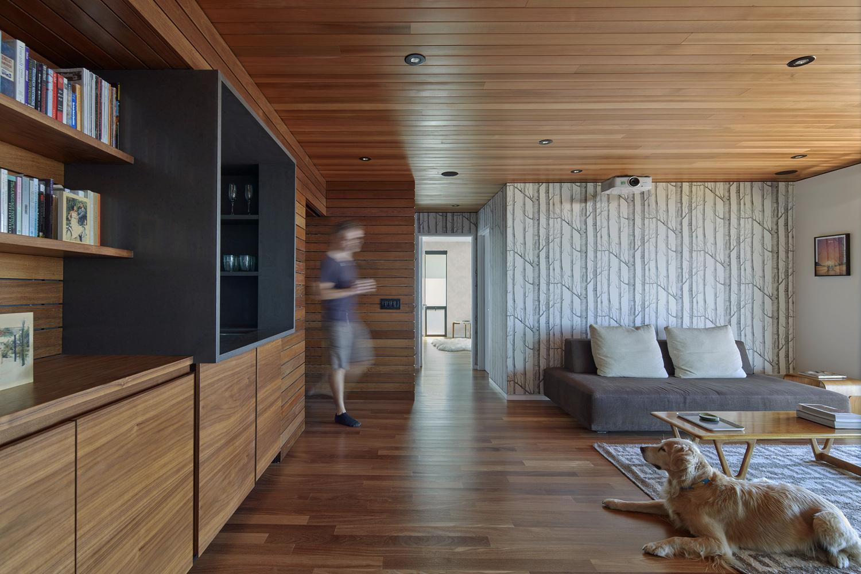 hình ảnh phòng khách với trần và sàn lát gỗ màu cánh gián, sofa ghi xám, chú chó nằm trên thảm