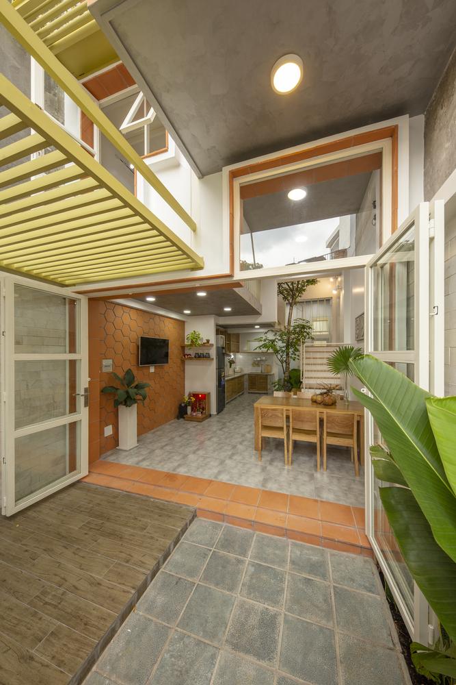 hình ảnh tầng trệt nhà mái đôi với cửa cao rộng, tường ốp gạch đỏ, bàn ăn bằng gỗ, phía trong là khu bếp nấu