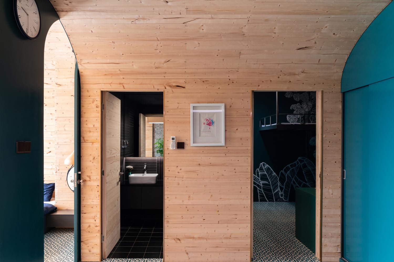 hình ảnh cửa vào phòng tắm, phòng ngủ nhìn từ bên ngoài với tường và trần khung vòm ốp gỗ màu sáng