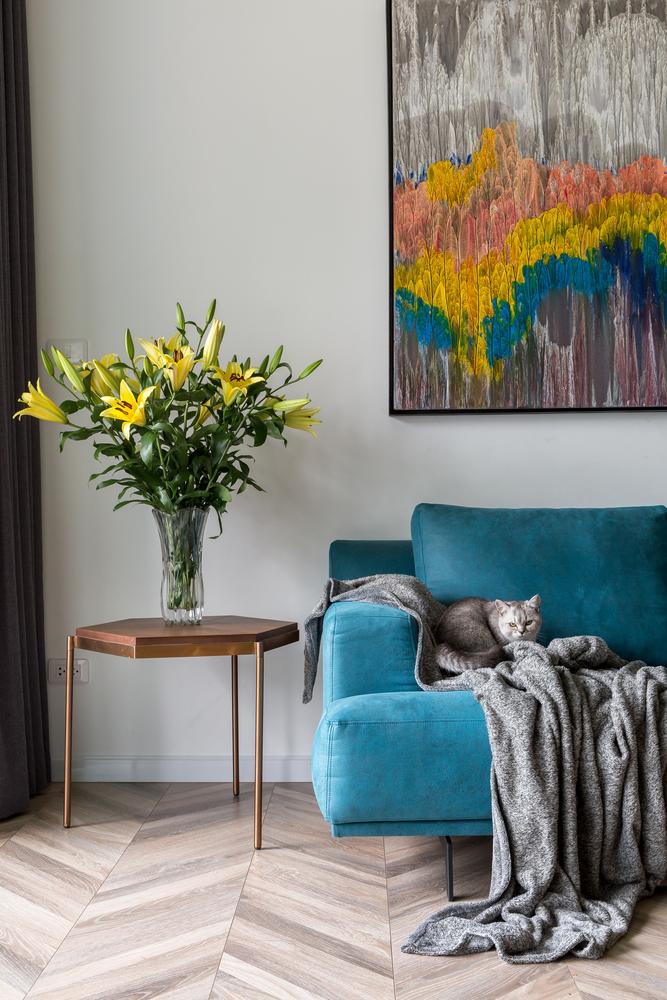 hình ảnh góc phòng khách hiện đại với sofa nhung màu xanh dương, tranh tường nghệ thuật, bàn phụ kim loại sáng bóng, trên bàn đặt bình hoa ly màu vàng
