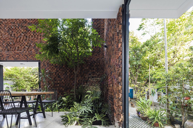 hình ảnh khuôn viên ngôi nhà ngập tràn cây xanh, tường gạch cháy độc đáo