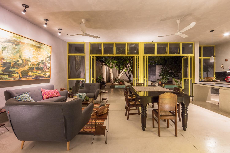 hình ảnh toàn cảnh phòng ăn kết hợp phòng ăn với sofa màu xám đậm, bàn ghế ăn bằng gỗ