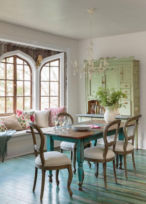 hình ảnh phòng ăn phong cách đồng quê với bàn gỗ màu xanh dương pastel, tủ lưu trữ xanh lá nhạt, cửa sổ kính dạng vòm, đèn chùm và bình hoa trang trí, ghế ngồi bên cửa sổ, gối tựa hoa văn màu sắc