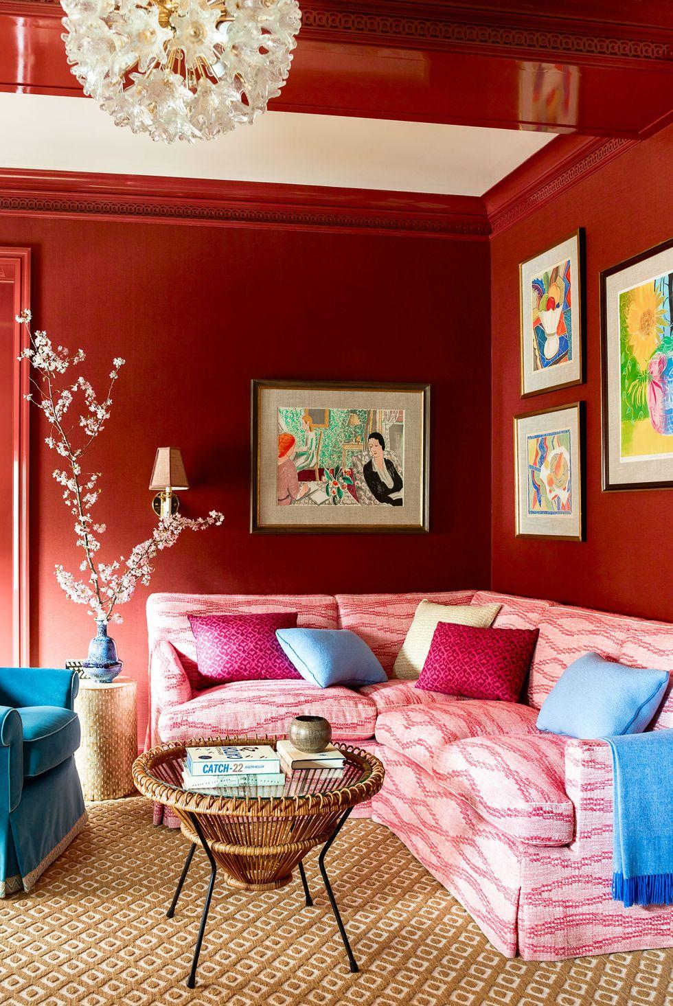hinh ảnh phòng khách nhỏ ấn tượng với tường sơn màu đỏ bóng, giúp làm nổi bật các tác phẩm nghệ thuật treo tường
