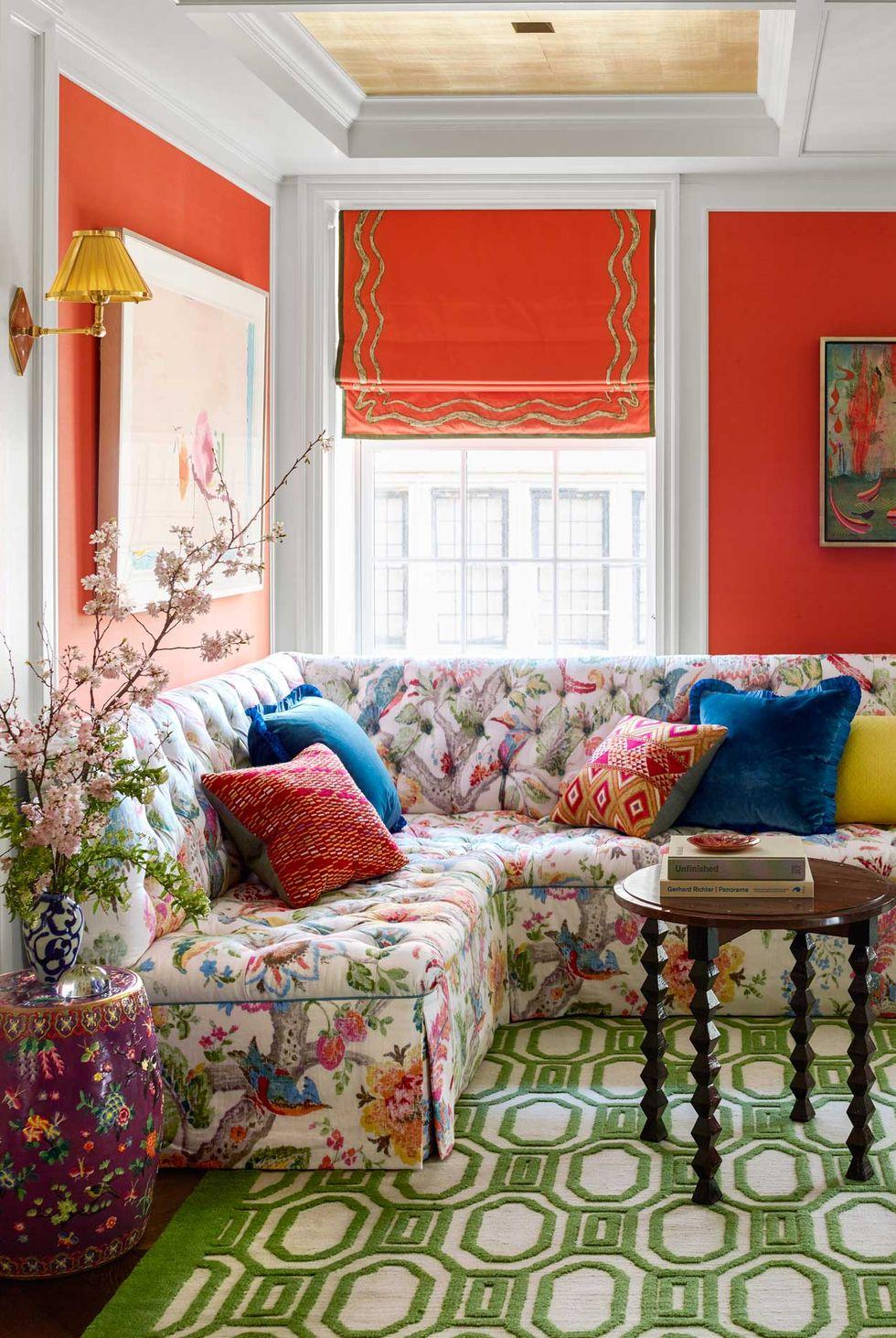 hình ảnh phòng khách nhiều màu sắc với sofa bọc vải hoa, thảm trải màu xanh lá, họa tiết hình học, bức tường màu cam tạo điểm nhấn