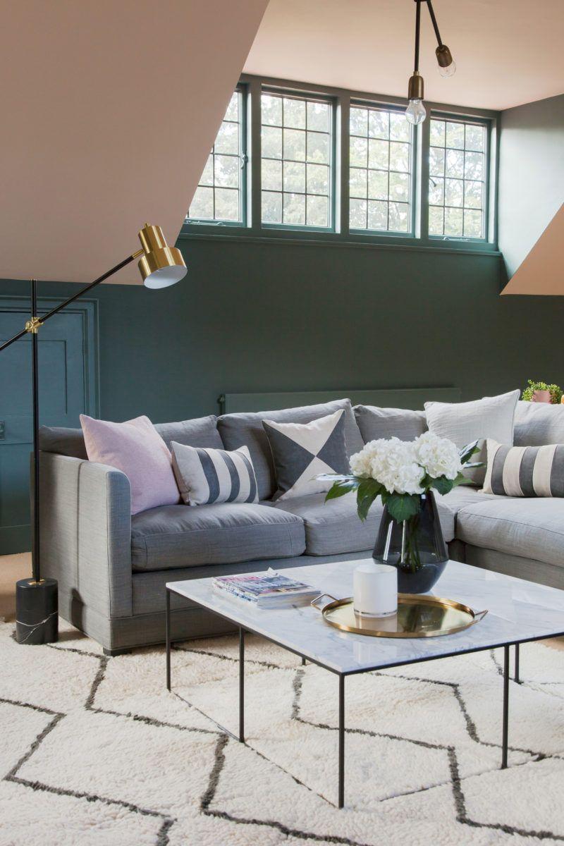 hình ảnh phòng khách nhỏ với tường sơn màu trung tính, sofa xám, nhiều gối tựa êm ái, bàn trà kính hình vuông đặt trên thảm trải lông mềm mại, họa tiết hình học bắt mắt