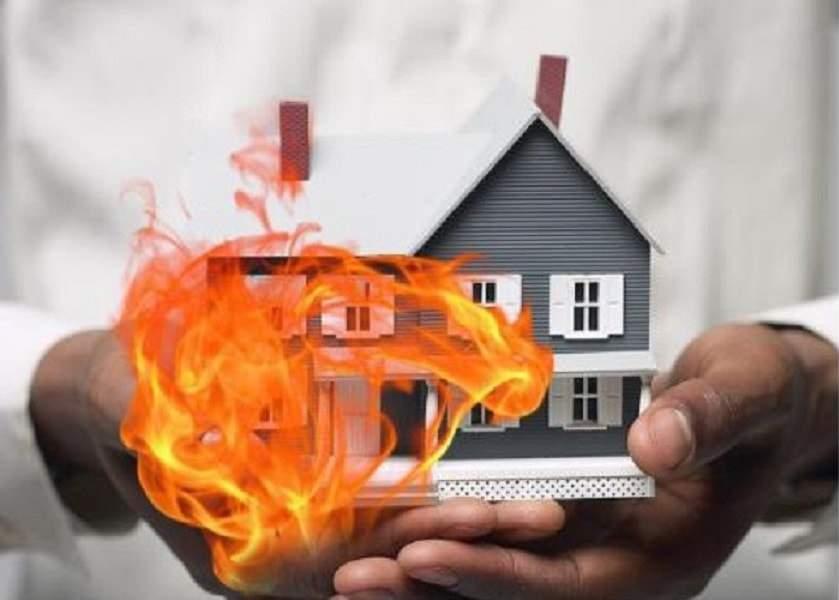 hình ảnh hai bàn tay cầm mô hình ngôi nhà, bên cạnh ngôi nhà có hình ngọn lửa bốc cháy