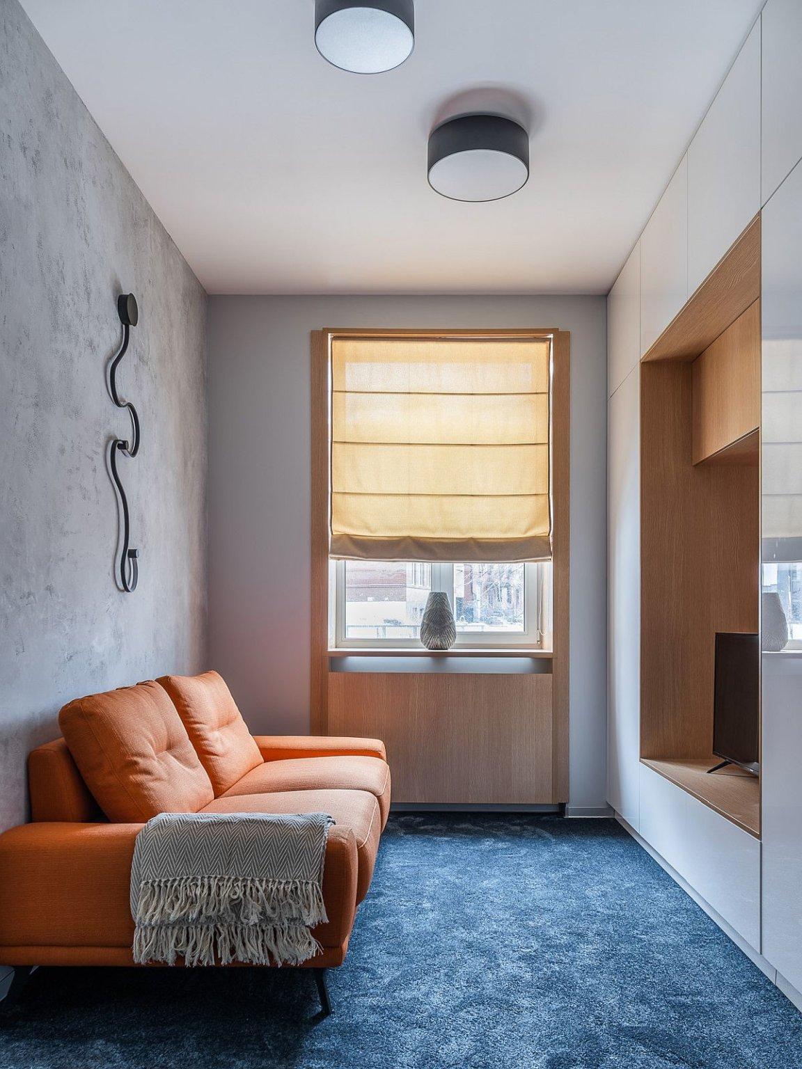 hình ảnh phòng khách tối giản với thảm trải màu xanh dương, ghế sofa màu nâu sáng, cửa sổ kính