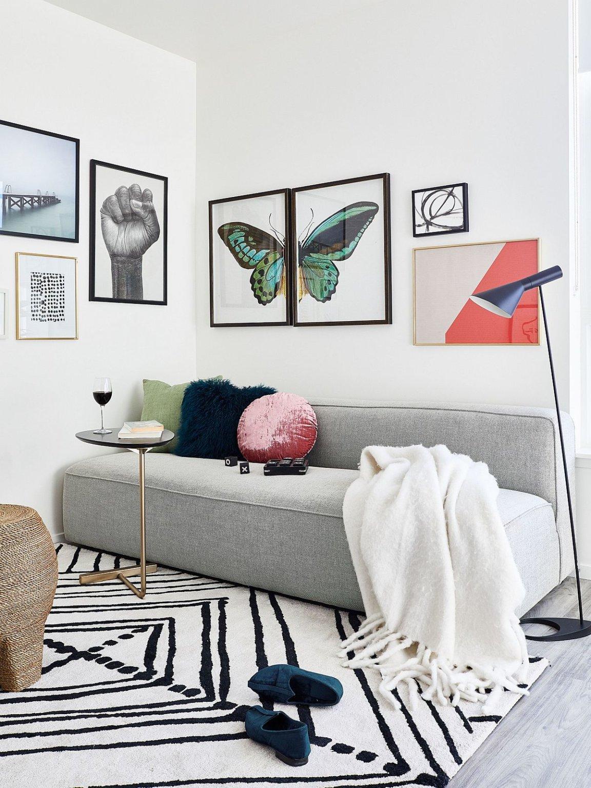 hình ảnh phòng khách với sofa ghi xám, bộ tranh treo tường họa tiết bướm, thảm trải họa tiết đen trắng