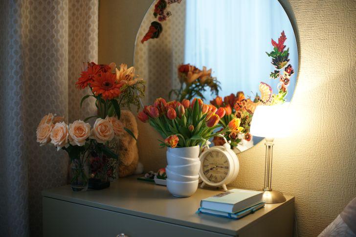 hình ảnh góc trang điểm xinh xắn với gương tròn dán nhãn tạo điểm nhấn, lọ hoa đồng tiền trên bàn