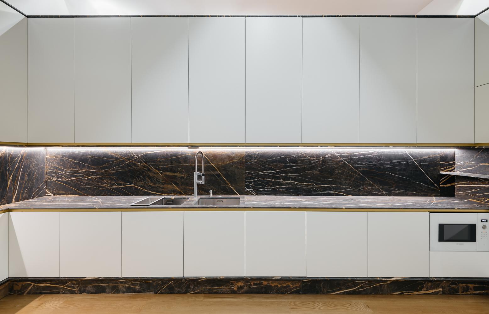 Hệ tủ bếp màu trắng không tay cầm tạo cảm giác thoáng đãng hơn cho không gian.