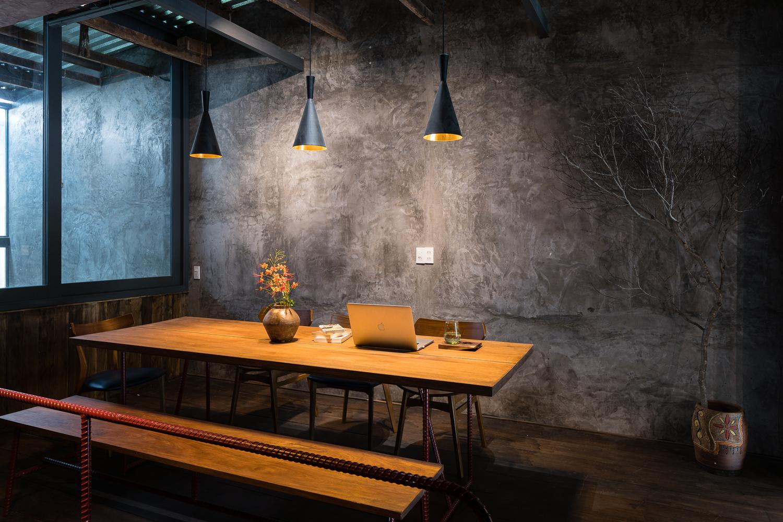 Ánh sáng đèn làm nổi bật sự tượng phản giữa chất liệu gỗ mà tường xi măng thô mộc.