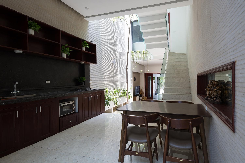 Nội thất gỗ sẫm màu tạo cảm giác ấm cúng cho không gian bếp nấu kết hợp phòng ăn.