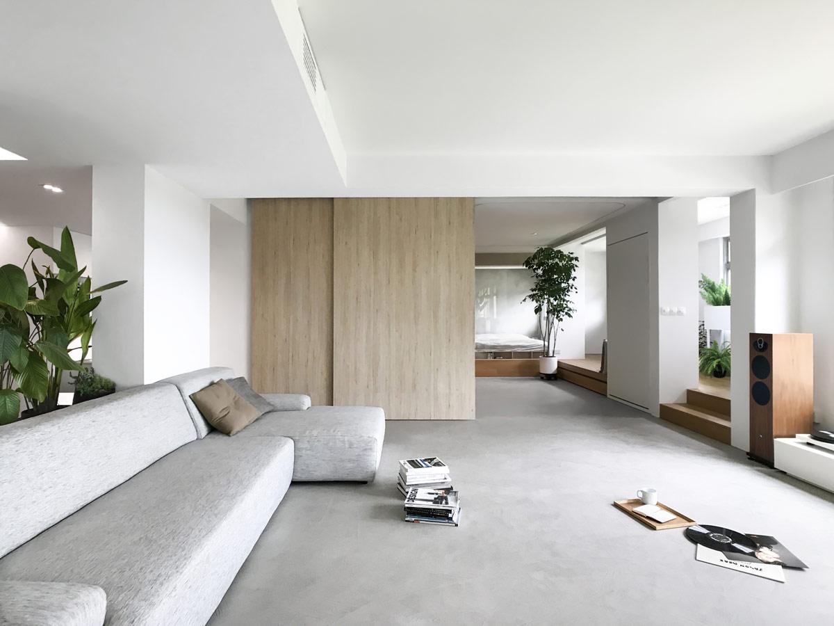 phòng khách đơn giản với sofa xám, cây xanh trang trí, vách ngăn trượt bằng gỗ