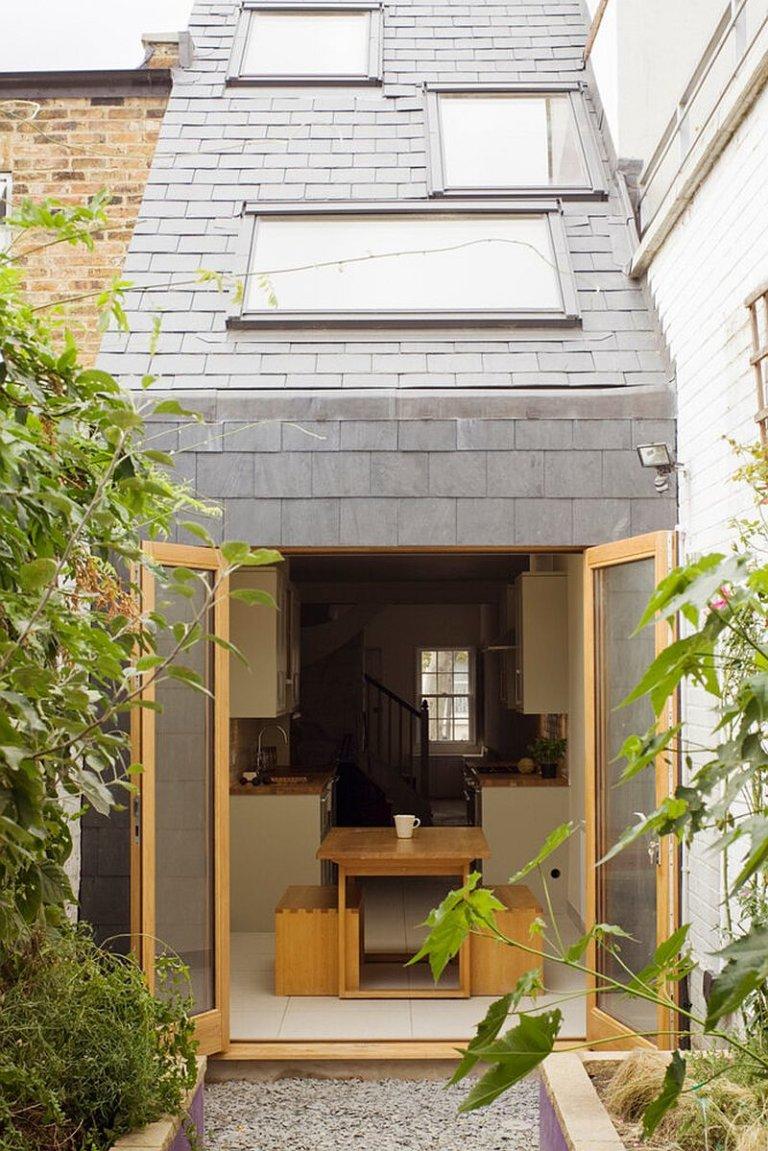 Ngôi nhà toát lên vẻ hiện đại và thanh lịch với ngoại thất màu xám, cửa kính khung gỗ và trần dốc có giếng trời so le.